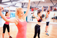 Group of people working out with barbells in gym. Fitness, sport, training, gym and lifestyle concept - group of smiling people working out with barbells in the Stock Photo