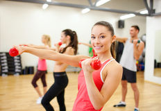 Group of people working out with dumbbells. Fitness, sport, training, gym and lifestyle concept - group of smiling people working out with dumbbells in the gym Stock Photo