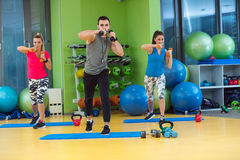 Group of people working out in a gym with a dumbbell Stock Photos