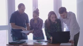 Group of people at the working place in a stylish office with large panoramic window. Handsome young man showing stock footage