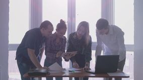 Group of people at the working place in a stylish office with large panoramic window. Handsome young woman uses touch stock footage