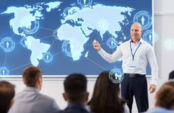 Group of people at world business conference. Business, global network and people concept - smiling businessman or lecturer with world map on projection screen royalty free stock images