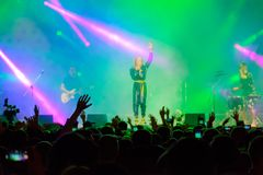 Group performing at live concert. Audience cheering at live concert stock images