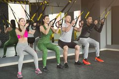 Group performing TRX suspension training in gym. Group of people performing TRX suspension training in gym. Sporty men and women doing exercise with elastic rope Stock Photos