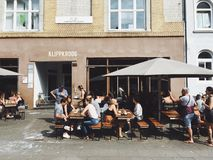 Group of Person Dining at Brown Wooden Outdoor Dining Set Beside Gray Concrete Building during Day Time Stock Photos