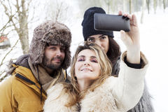 Group of person taking selfie in winter forest Royalty Free Stock Image