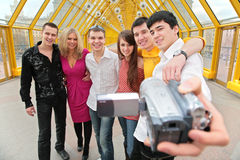 Group of persons removes itself to video. Group of young persons removes itself to video camera on footbridge Royalty Free Stock Photography