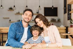 Group photo of beautiful young family with little curly kid. In cafe stock photography