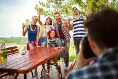 Group photo with birthday girl and friends with raise glasses. Cheers in nature Stock Photography
