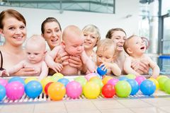 Group picture of mothers and babies at infant swimming class. Group of moms and their little babies at baby swimming lesson royalty free stock images
