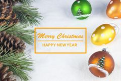 Group of pine trees, some branches and colorful baubles and Christmas balls with text in English `Merry Christmas, happy new year`. In white snow background stock images