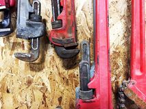 Group of pipe wrenches hanging on wooden wall. Stock Photography