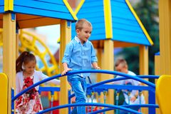 Group of playful kids having fun on toy castle, on playground Stock Image