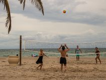 Group playing volley ball on a beautiful beach. Hollywood , Florida - January 10, 2018: Group of beach goers playing volley ball on the beach with ocean in Stock Photo