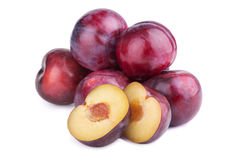 Group of plum fruits and a half on white. Background Royalty Free Stock Image