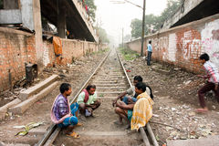 Group of poor men sit on the railroad tracks. KOLKATA, INDIA: Group of poor men sit on the railroad tracks and have conversation. Third biggest indian city Stock Photo