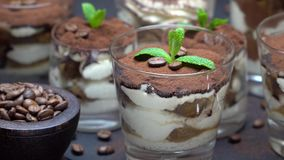 Group of portions of classic tiramisu dessert in a glass cup on stone board on concrete background. Or table stock video