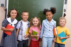 Group portrait. Image of curious schoolchildren standing by blackboard and looking at camera in the classroom Stock Photography