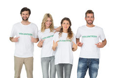 Group portrait of happy volunteers pointing to themselves Stock Image