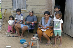 Group portrait of Indian family in a slum. Bolivia, city of Santa Cruz: Indian parents with their children sitting and standing for their meager adobe house in a Stock Photos