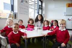 Group portrait of infant school teacher and kids sitting at table in a classroom looking to camera smiling, front view stock images