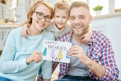 Happy Family Celebrating Fathers Day. Group portrait of loving young family sitting on carpet of modern living room and showing handmade greeting card for royalty free stock photography