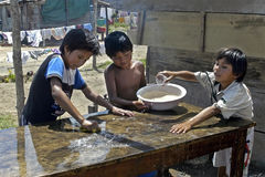 Group portrait of a table cleaning boys, Bolivia. Three Bolivian boys help their mother by cleaning, with soapy water, a table in a shabby slum, in a very poor Stock Image