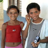 Group portrait of teens, Conde, Brazil. The boy and girl both have a headphone in their ears. They share the headphones which is connected to a portable radio Royalty Free Stock Image