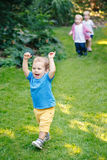 Group portrait of three white Caucasian blond adorable cute kids playing running in park garden outside Royalty Free Stock Photography