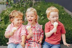 Three white Caucasian cute adorable funny children toddlers sitting together sharing ice-cream food. royalty free stock image