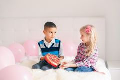 Boy giving girl chocolate gift present to celebrate Valentine Day. Group portrait of two Caucasian cute adorable children eating heart shaped candies. Boy giving stock images