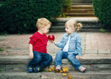 Group portrait of two white Caucasian cute adorable funny children toddlers sitting together sharing apple food. Love friendship childhood concept, best Royalty Free Stock Photo