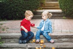 Two white Caucasian cute adorable funny children toddlers sitting together sharing eating apple food