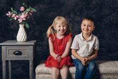 Two white Caucasian prescholler boy and girl sitting together on couch indoors. Children smiling laughing together royalty free stock photo