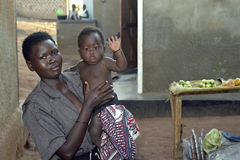 Group portrait of Ugandan mother with child. Uganda, village Kalasa: a woman proudly poses with her baby in front of market stall. The young child is waving Stock Photos
