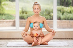 Group portrait of white Caucasian mother and baby daughter doing physical fitness exercises yoga together sitting in lotus pose on Stock Photo
