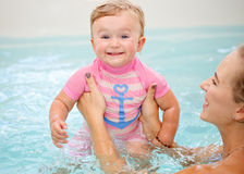 Group portrait of white Caucasian mother and baby daughter playing in water diving in swimming pool inside, looking in camera, tra Royalty Free Stock Photography