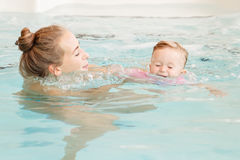 Group portrait of white Caucasian mother and baby daughter playing in water diving in swimming pool stock photography
