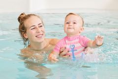 Group portrait of white Caucasian mother and baby daughter playing in water diving in swimming pool inside, training to swim stock images