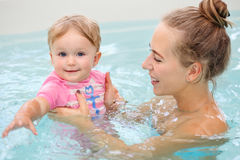 Group portrait of white Caucasian mother and baby daughter playing in water diving in swimming pool inside, training to swim, heal Royalty Free Stock Photography