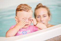 Group portrait of white Caucasian mother and child daughter playing in water diving in swimming pool Stock Images