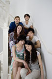 Group portrait of young friends sitting in stairway Royalty Free Stock Photo