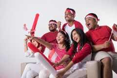 Indonesian supporter watching with excitement. Group portrait of young indonesian supporter people watching soccer match with excitement stock photography