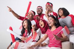 Indonesian supporter watching with excitement. Group portrait of young indonesian supporter people watching soccer match with excitement stock photo