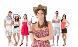Group portrait of young people in summer clothing. Group portrait of happy young people dressed for summer. Young women at front holding sunglasses Stock Image
