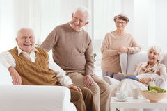 Group of positive seniors. Sitting at light home interior stock image