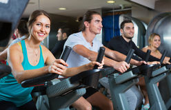 Group positive working out of cycling in fitness club. Group positive happy working out of cycling in modern fitness club Stock Photos