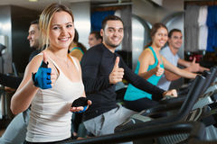 Group positive working out of cycling in fitness club. Group positive smiling working out of cycling in modern fitness club Royalty Free Stock Photos