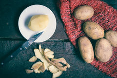Group of potatoes. One peeled potato, some peels and group of raw potatoes on the table Stock Photography