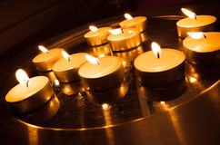 Group of pray candles burn on a metal stand Royalty Free Stock Images